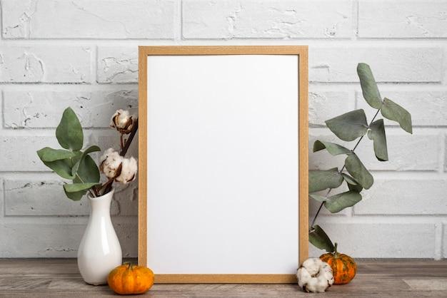Leeg frame naast vaas met katoen