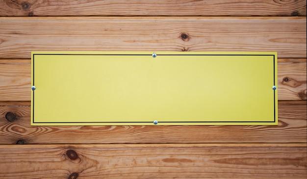 Leeg geel naamplaatje op een houten bord
