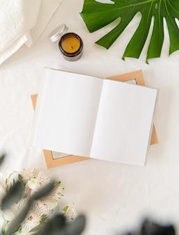Leeg geopend boek, kaarsen, bloemen en palmblad over een wit bed, plat gelegd