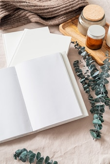 Leeg geopend boek, kaarsen en eucalyptusbladeren op wit bed, plat gelegd