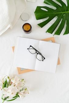 Leeg geopend boek, kaarsen, glazen, bloemen en palmblad over een wit bed, plat gelegd