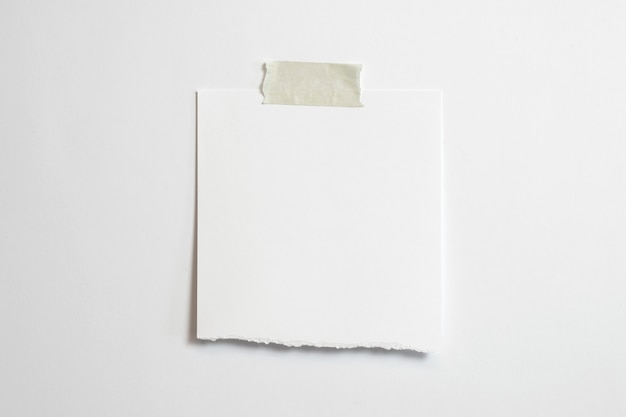 Leeg gescheurd polaroidfotokader met zachte schaduwen en plakband dat op witboekachtergrond wordt geïsoleerd