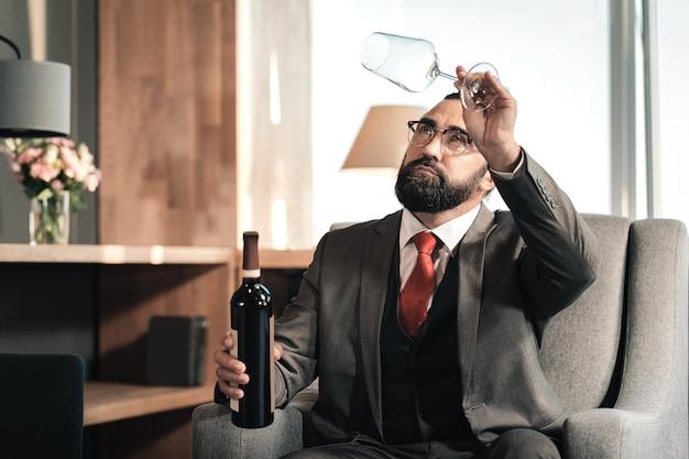 Leeg glas. bebaarde donkerharige volwassen man leeg glas wijn kijken alvorens te drinken