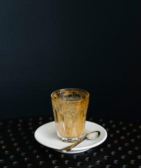Leeg glas koffie met een schotel en een lepel
