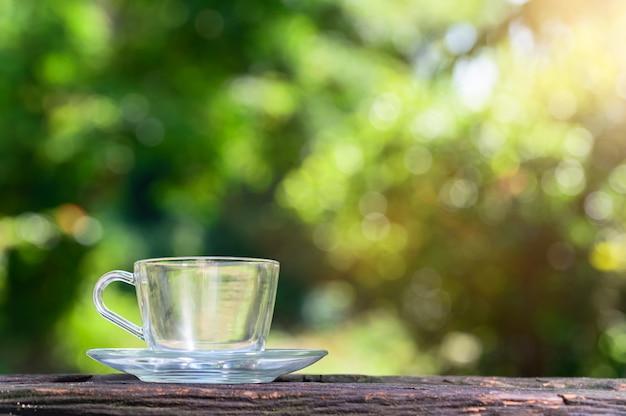 Leeg glas leeg op de houten zon van het vloerscène bokeh groen licht