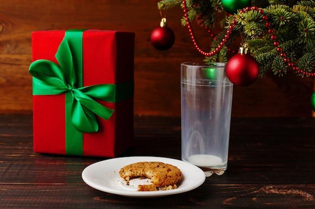 Leeg glas melk en kruimelkoekjes en een geschenk onder de kerstboom. de komst van de kerstman.