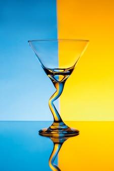 Leeg glas over blauwe en gele muur