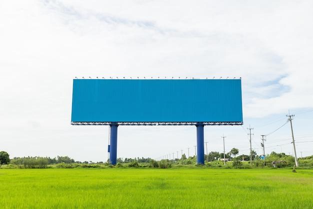 Leeg groot wit reclameaanplakbord in groen padieveld