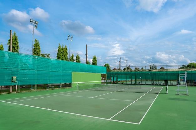 Leeg hard tennisbaan en netto openlucht met blauwe hemelwolken op een zonnige dag.