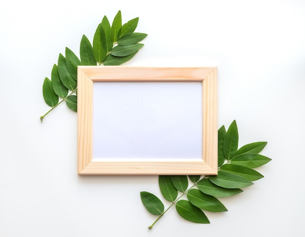 Leeg houten fotoframe met groene bladeren