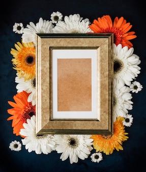 Leeg houten fotolijstje op verse kleurrijke madeliefjesachtergrond