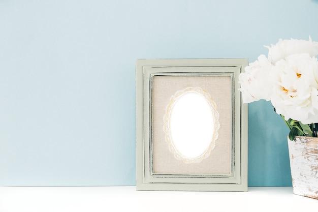 Leeg houten frame en bloemen in vaas op lijst aangaande blauwe achtergrond.