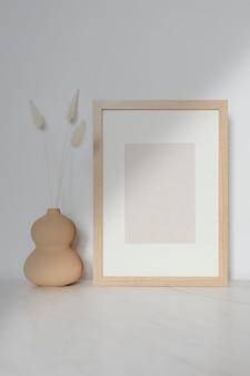 Leeg houten frame met gedroogde bloemen in een kalebasvaas