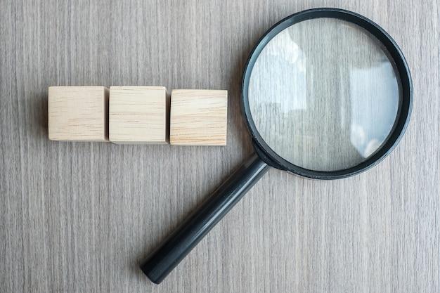 Leeg houten kubussen en vergrootglas op houten lijst