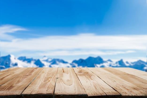 Leeg houten oppervlak op onscherpe achtergrond van besneeuwd bergachtig gebied op winterdag en blauwe lucht