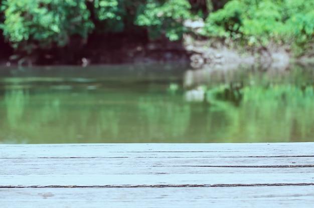 Leeg houten plankterras over groene rivier en bosachtergrond