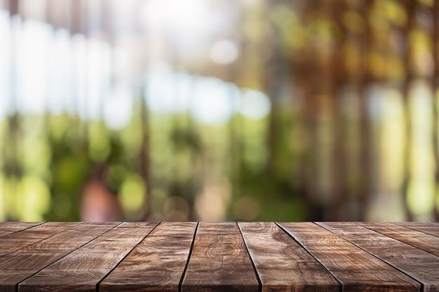 Leeg houten tafelblad en wazig koffieshop