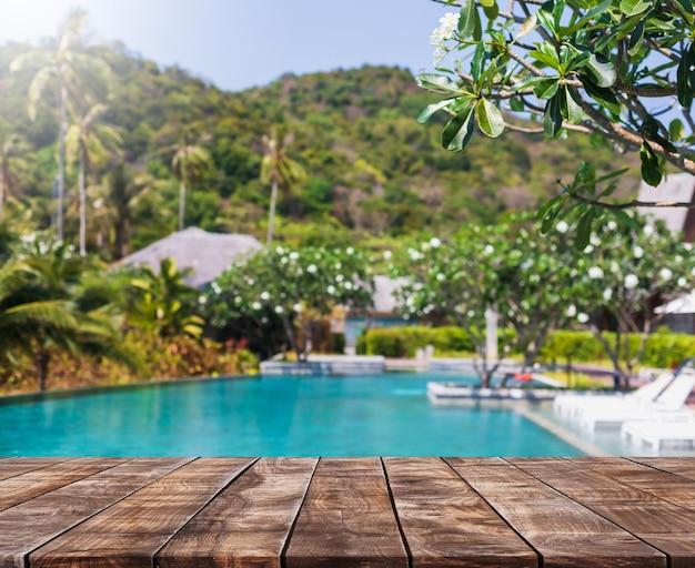 Leeg houten tafelblad en wazig zwembad in tropisch resort op zomerbannerachtergrond - kan worden gebruikt voor het weergeven of monteren van uw producten.
