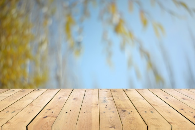 Leeg houten tafelblad met boomtak vage achtergrond