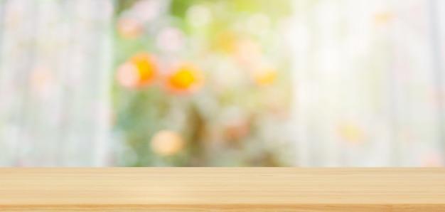 Leeg houten tafelblad met onscherpte wit gordijnraam en groene tuin voor productweergavesjabloon