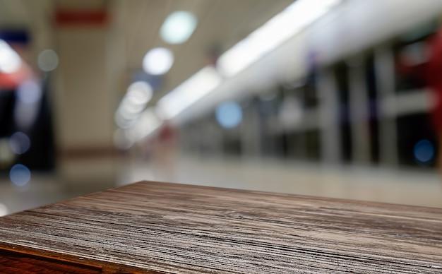 Leeg houten tafelruimte platform en wazige koffie winkel waar werk en ontmoetingsplaats achtergrond voor product display montage. selectieve focus.