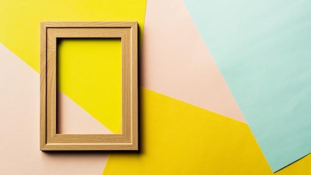 Leeg klassiek houten fotokader op roze, gele en blauwe achtergrond.