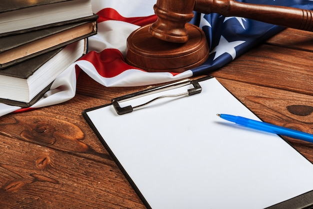 Leeg klembord en de vlag van de vs op houten tafel