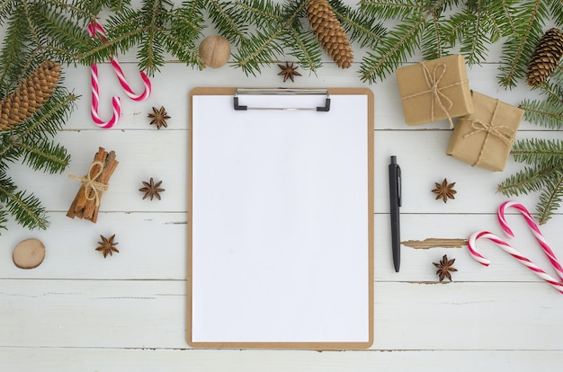 Leeg klembord, kerstmisdecoratie op witte houten achtergrond. plat leggen, bovenaanzicht mock-