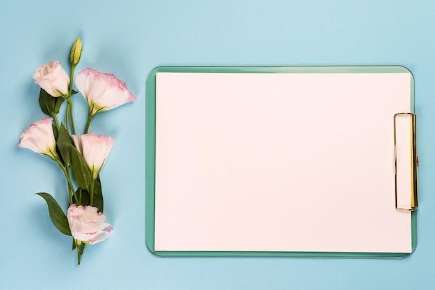 Leeg klembord met papier en boeket bloemen eustoma, bovenaanzicht