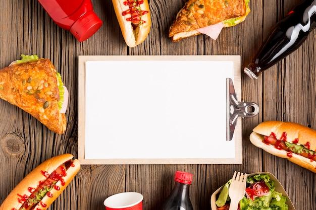 Leeg klembord omringd door fast food
