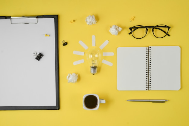 Leeg klembord, pen, blocnote, oogglazen, kop van koffie, gloeilamp op gele achtergrond.