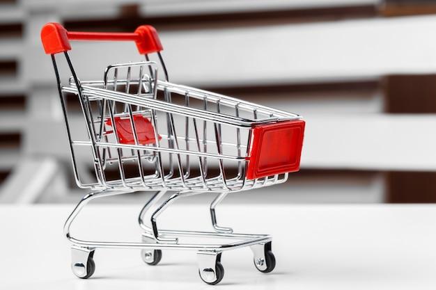 Leeg kruidenierswinkelstuk speelgoed boodschappenwagentje op een lijst