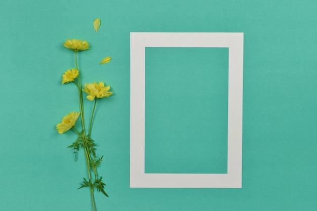 Leeg leeg fotopapier frame met gele bloem aan de zijkant.