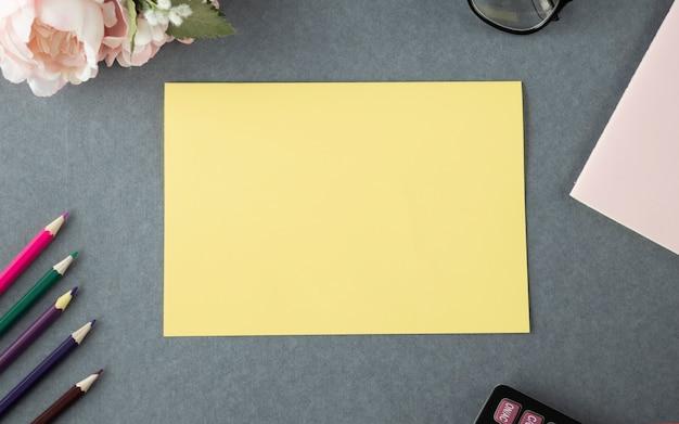 Leeg leeg geel papier mock up op een houten tafel in de buitenlucht.
