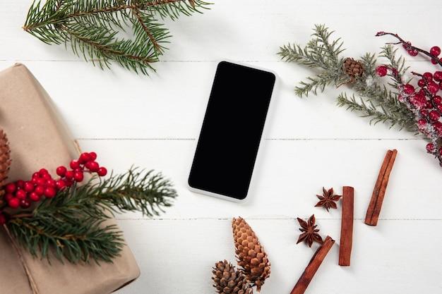 Leeg leeg scherm van smartphone op de witte houten muur met kleurrijke vakantie decoratie en geschenken.