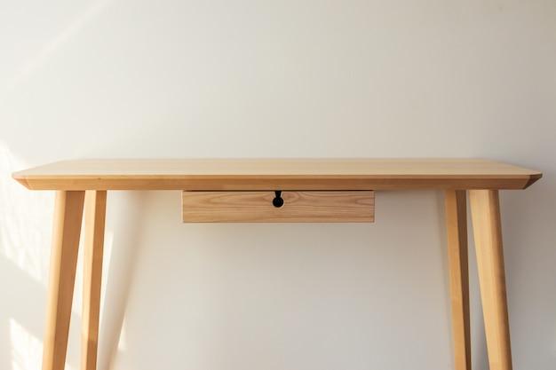 Leeg licht houten tafelblad met witte muur achtergrond