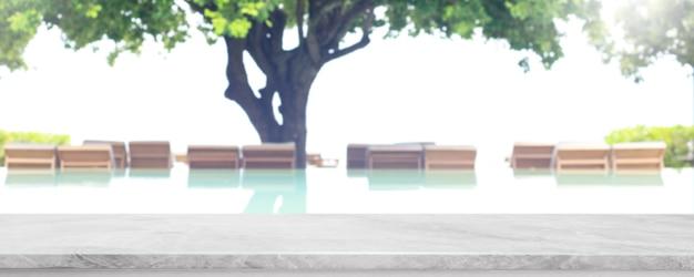 Leeg marmeren stenen tafelblad en wazig zwembad in tropisch resort op zomerbannerachtergrond - kan worden gebruikt voor het weergeven of monteren van uw producten.