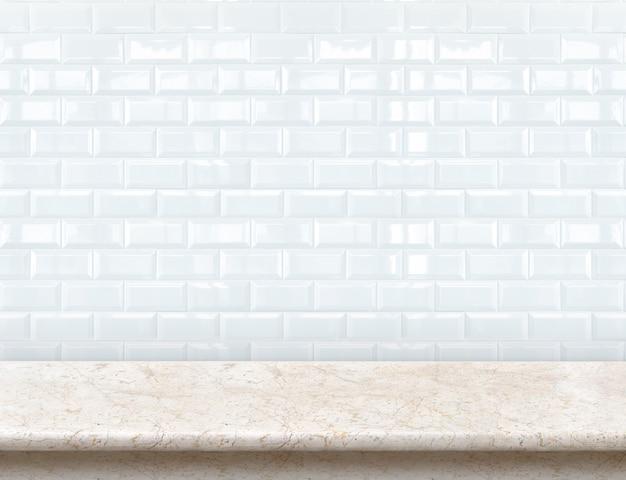 Leeg marmeren tafelblad met glanzende keramische witte tegelmuur.