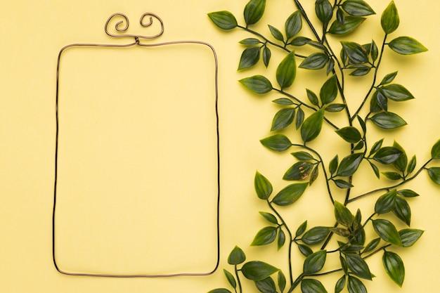 Leeg metaalframe dichtbij de kunstmatige bladeren op gele muur