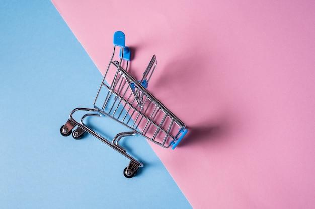 Leeg miniatuurboodschappenwagentje op blauwe en roze kleurenachtergrond.