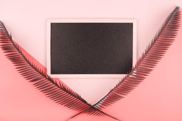 Leeg miniatuurbord dat met palmbladen over de roze en koraalachtergrond wordt verfraaid