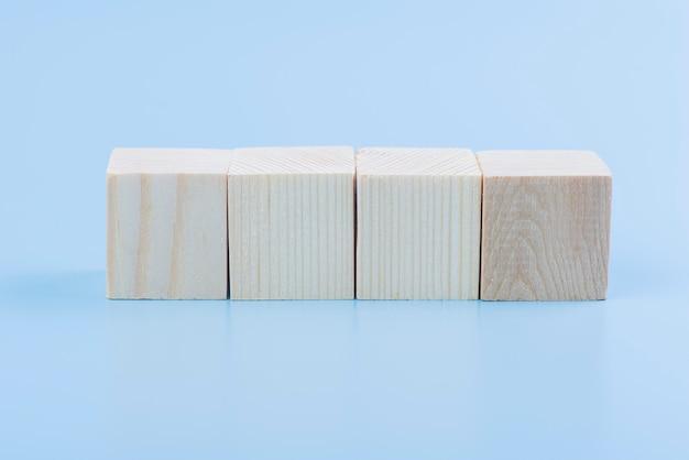 Leeg natuurlijk houten kubusblok op blauwe achtergrond