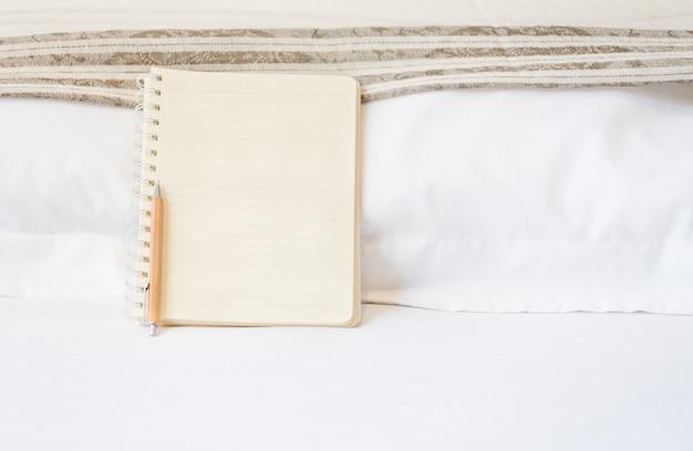 Leeg notbook en houten potlood op wit bed