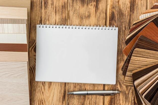 Leeg notitieblok met houten vloercatalogus voor een nieuw ontwerp van uw huis. plank laminaat collectie voor decoratie interieur
