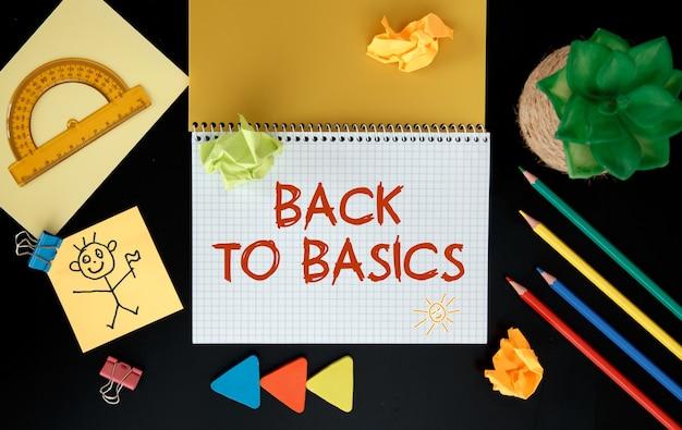 Leeg notitieblok met tekst back to basics op een bureau met kantooraccessoires