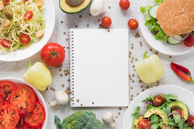 Leeg notitieboekje dat door heerlijk veganistisch voedsel wordt omringd