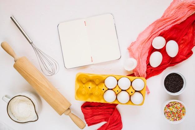 Leeg notitieboekje dichtbij kokende ingrediënten en hulpmiddelen