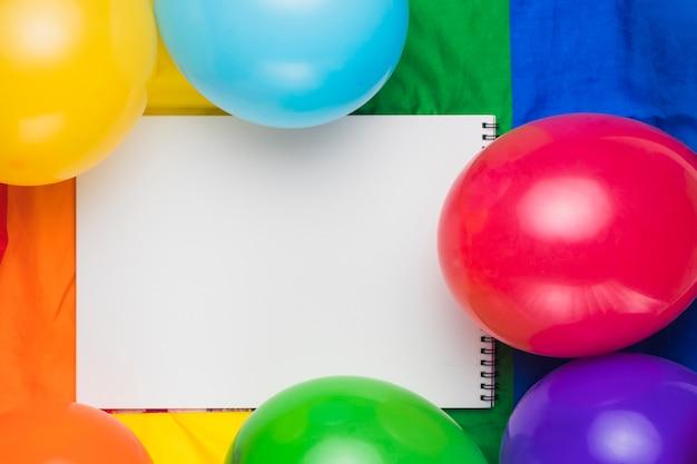 Leeg notitieboekje en kleurrijke ballons