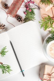 Leeg notitieboekje en potlood voor wensen, takenlijst, koffiemok, kerstcadeau of huidige doos, versierd met kerstboomtakken, dennenappels, rode bessen, op witte marmeren tafel, kopie ruimte bovenaanzicht