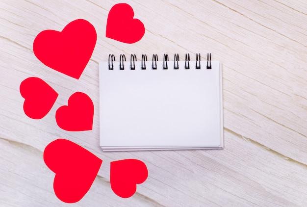 Leeg notitieboekje en rode harten op houten.